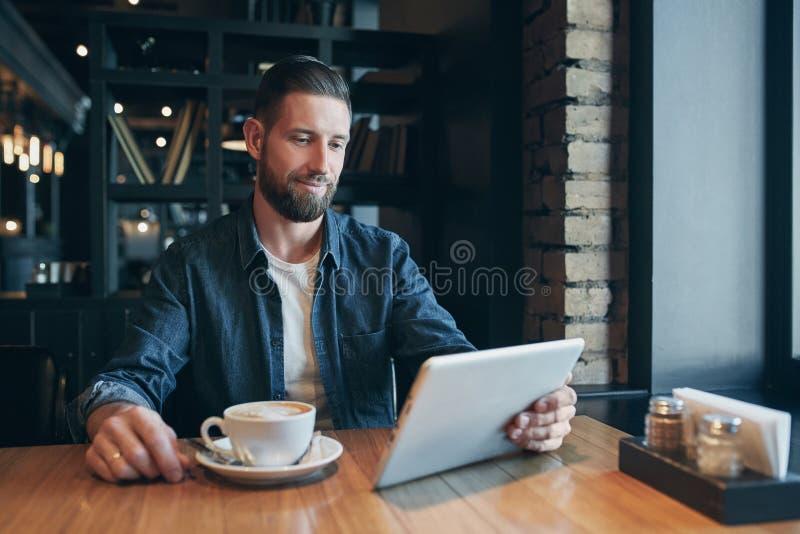 Café bebendo do homem novo no café e no tablet pc da utilização fotografia de stock royalty free