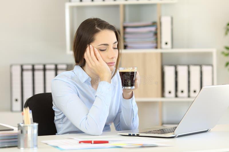 Café bebendo executivo sonolento no escritório fotografia de stock royalty free