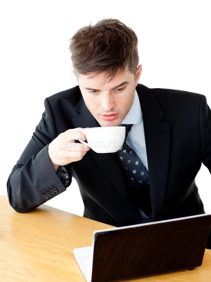 Café bebendo forçado do homem de negócios usando o portátil imagens de stock