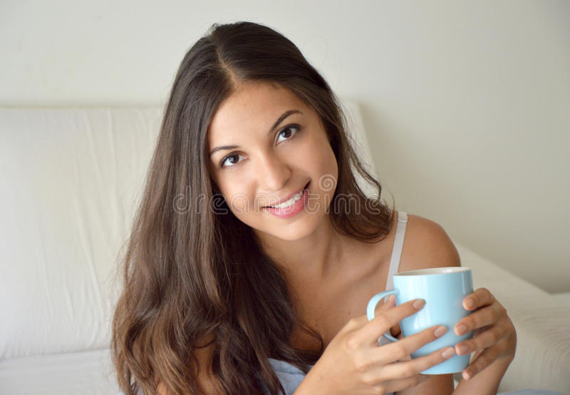 Café bebendo ou chá da menina bonita do retrato na cama na manhã no apartamento com espaço da cópia imagem de stock royalty free