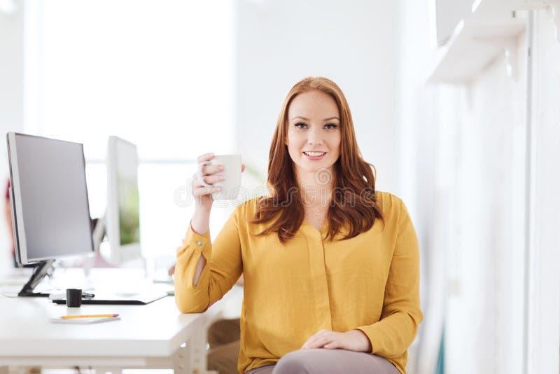 Café bebendo ou chá da mulher feliz no escritório fotos de stock royalty free
