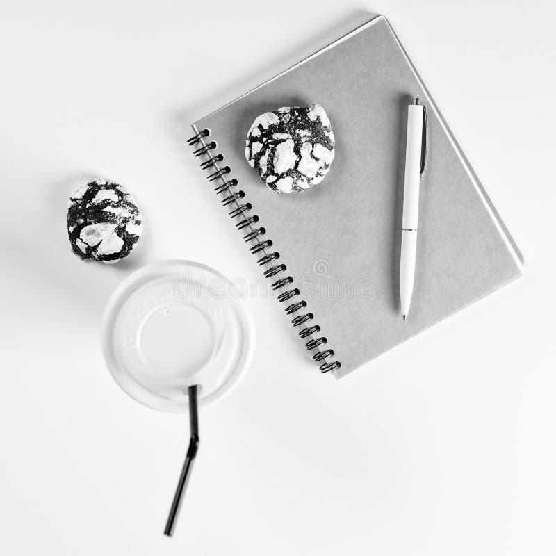 Café, biscuits, carnet propre et stylo sur le bureau blanc Maquette confortable de petit déjeuner style plat de configuration Con image stock