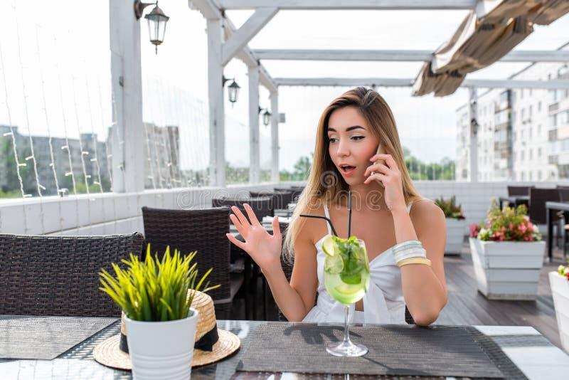 Café blanco del verano del vestido de la mujer que llama el teléfono, choque sorprendido, desconcierto Placer de la sorpresa, sma fotografía de archivo libre de regalías