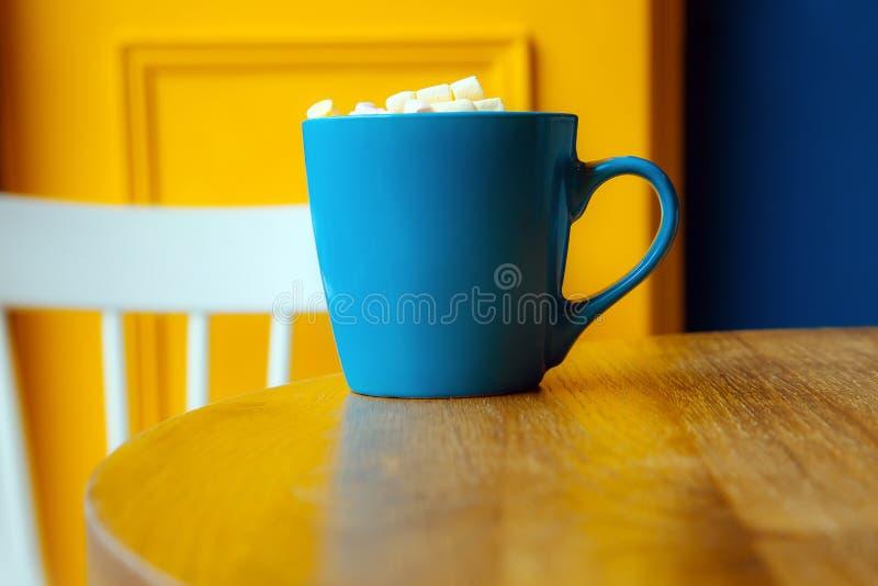 Café bleu de guimauve de fenêtre de chaise de table de fond de jaune de tasse de café image stock
