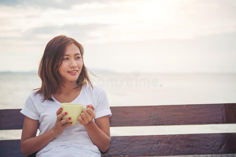 Café bonito da bebida da mulher ao sentar-se no balanço na praia foto de stock royalty free