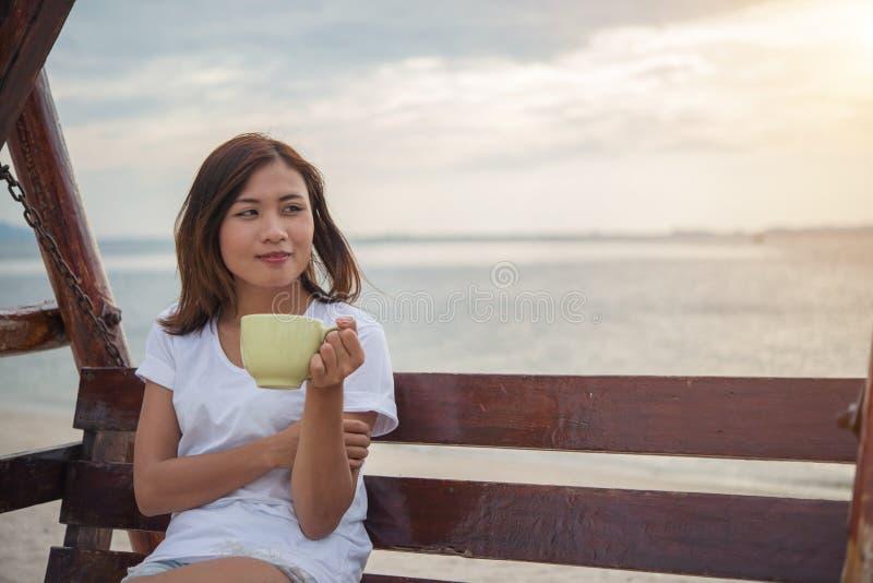 Café bonito da bebida da mulher ao sentar-se no balanço na praia imagens de stock royalty free