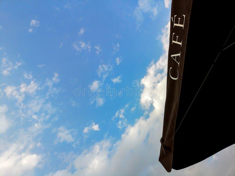 CAFÉ - Cafézeichen auf einem schwarzen Regenschirm gegen den blauen Himmel und die Wolken lizenzfreies stockfoto