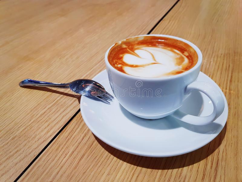 Café caliente con espuma cremosa del modelo de la hoja en la taza blanca foto de archivo libre de regalías