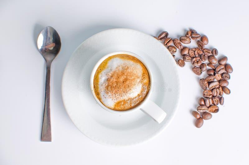 Café caliente con las habas en un fondo blanco fotos de archivo libres de regalías