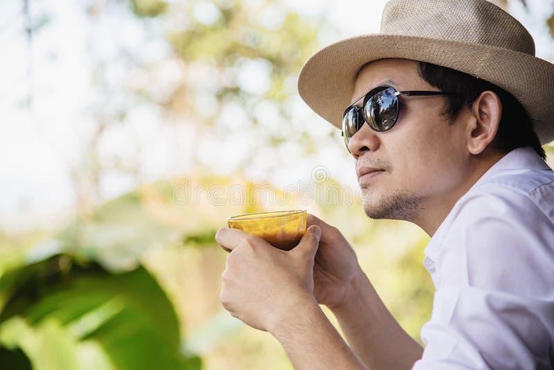 Café caliente de la bebida asiática casual del hombre feliz en naturaleza fotos de archivo