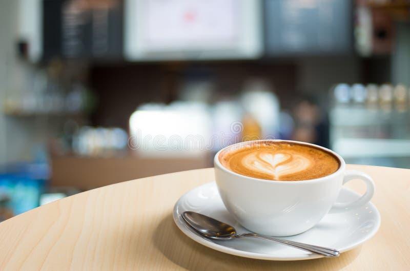 Café caliente del Latte del arte en una taza en la tabla y la cafetería de madera bl fotografía de archivo libre de regalías