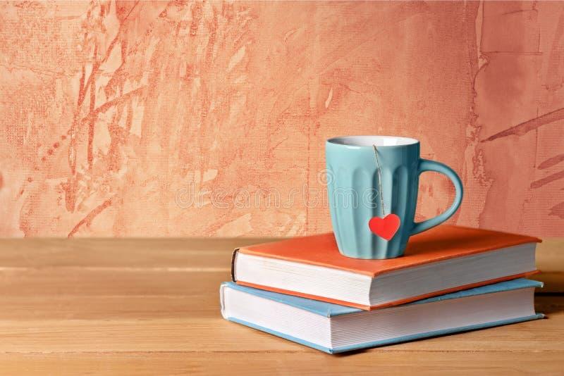 Café caliente en taza con los libros en fondo del vintage imágenes de archivo libres de regalías