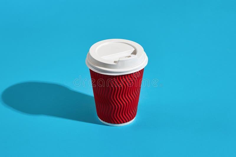Café caliente en taza de papel roja con la tapa blanca en los wi azules del fondo fotos de archivo