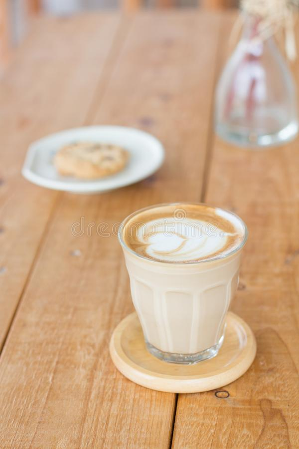Café caliente en un estilo retro de la taza de cristal que coloca en la tabla de madera imagen de archivo