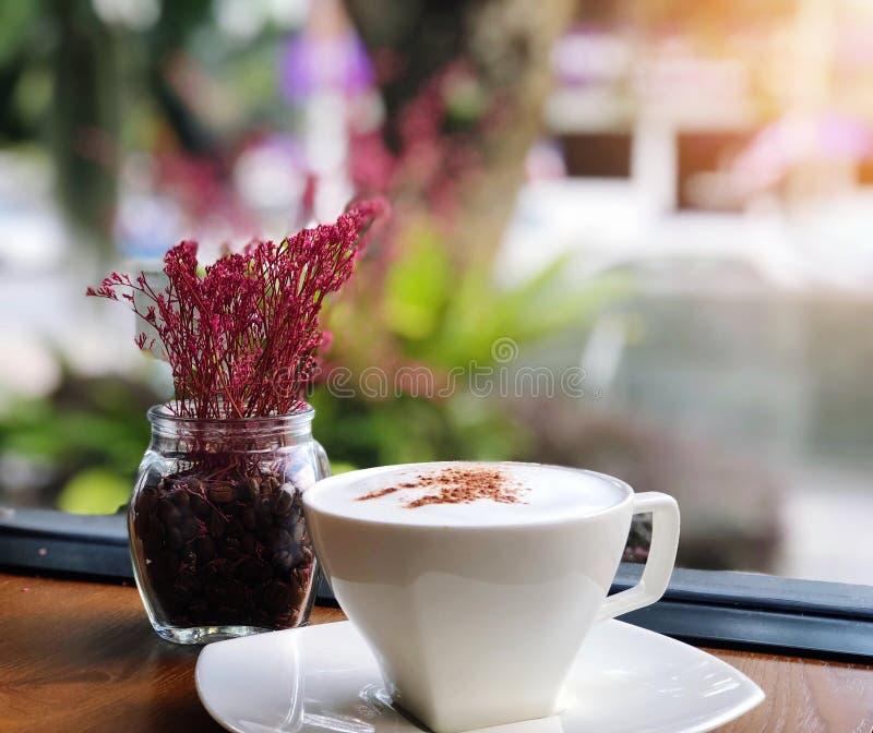 Café caliente en una taza blanca en la tabla y el florero de madera en fondo de la falta de definición de la cafetería imágenes de archivo libres de regalías