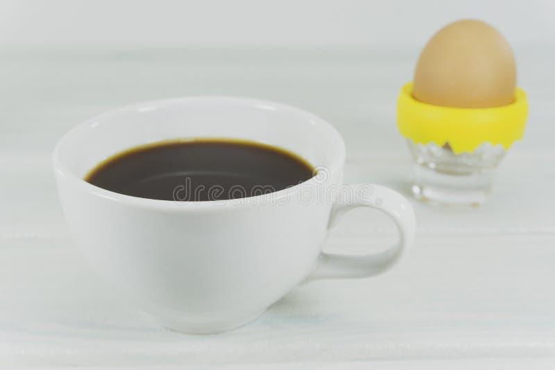 Café caliente por la mañana con el huevo pasado por agua en taza en un blanco de madera imagen de archivo libre de regalías
