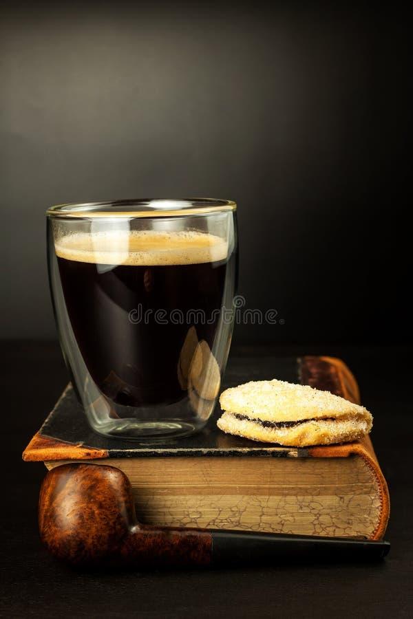 Café caliente y un libro en la tabla Tubo que fuma viejo fotografía de archivo