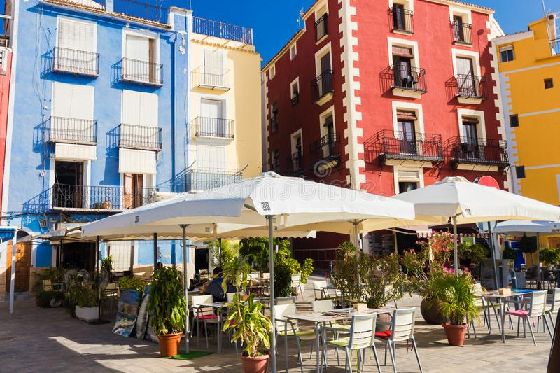 Café, casas coloridas e palmas na rua em Villajoyosa, Espanha em um dia ensolarado fotografia de stock royalty free