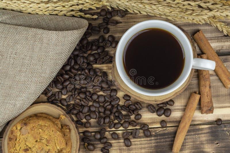 Café chaud étendu par appartement avec des grains de café sur la table en bois image stock