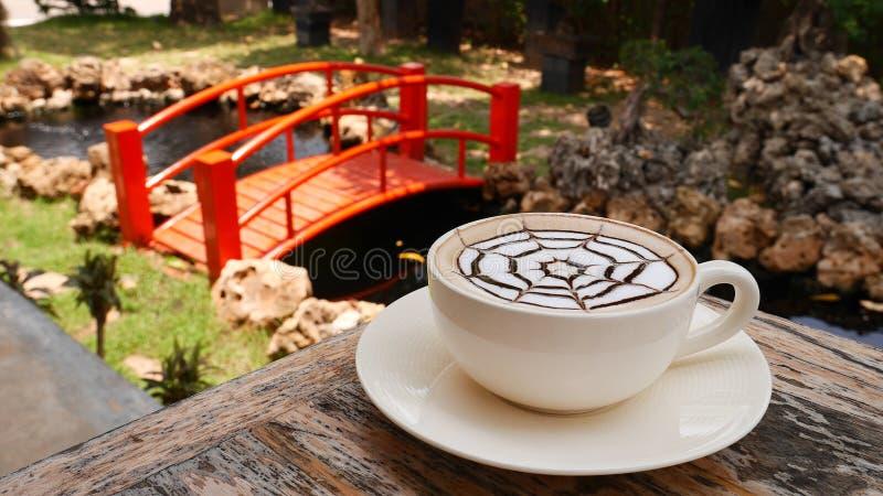 Café chaud d'art de latte dans le jardin japonais et le pont rouge images stock