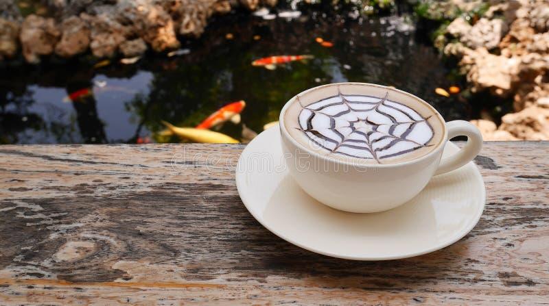 Café chaud d'art de latte sur la table en bois près de l'étang à poissons de carpe dans le style japonais de jardin images libres de droits