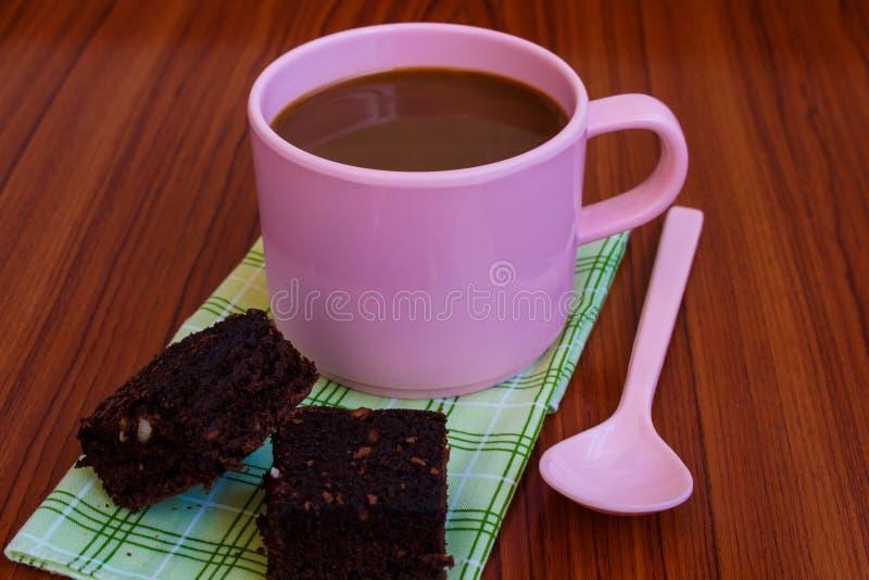 Café chaud dans la tasse rose avec le 'brownie' photographie stock