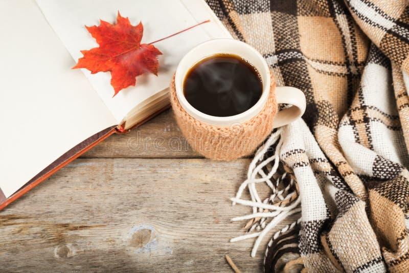 Café chaud dans une grande tasse, livre, feuille d'érable, plaid image stock