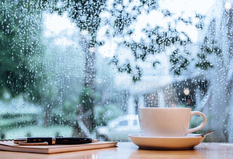 Café chaud de foyer de tasse blanche molle de tache floue sur la fenêtre en bois de table avec la goutte de pluie Copiez l'espace photos libres de droits