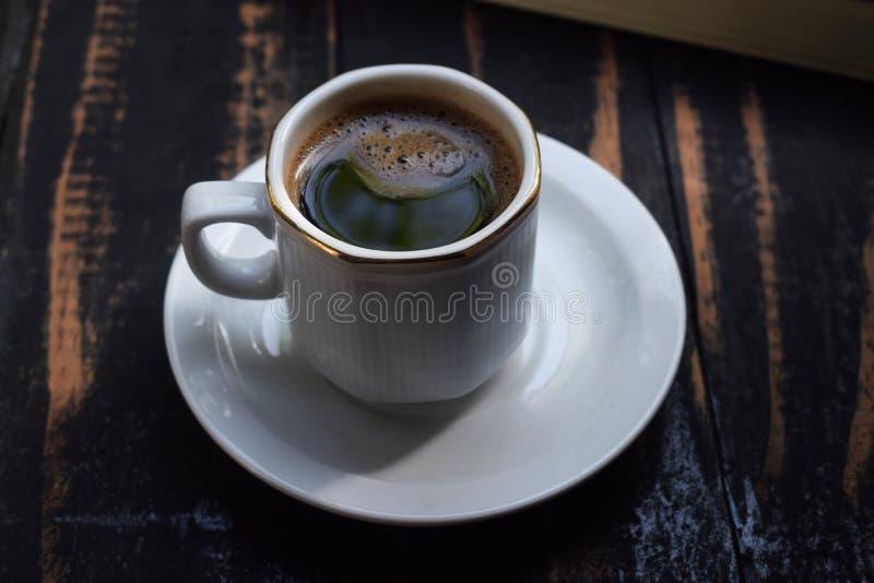 Café chaud de matin sur la table près du livre photographie stock libre de droits