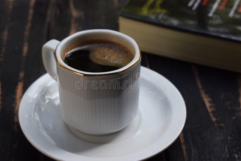 Café chaud de matin sur la table près du livre photo stock