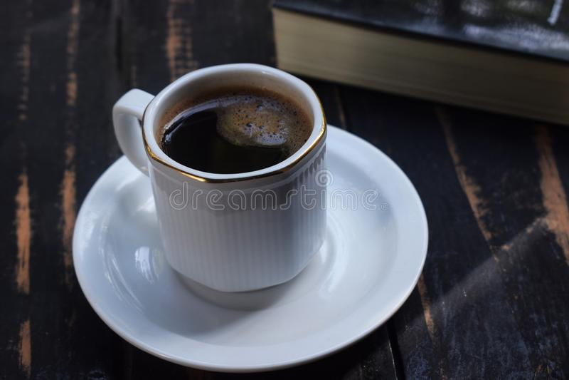 Café chaud de matin sur la table près du livre photos libres de droits