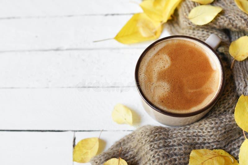Café chaud et feuilles d'automne sur fond de bois blanc - concept de détente saisonnier photo libre de droits