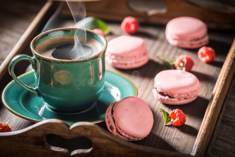 Café chaud et macarons roses savoureux faits de framboises fraîches image stock