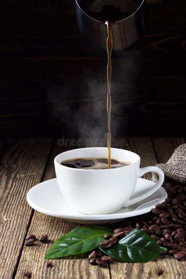 Café chaud se renversant dans la tasse blanche images libres de droits