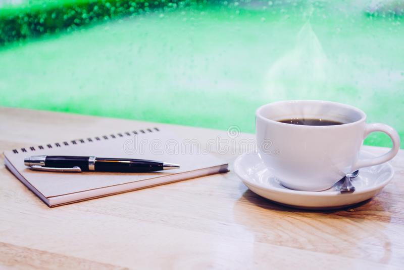 Café chaud sur la tasse blanche avec de la fumée, le bureau de travail avec le stylo et le carnet images libres de droits
