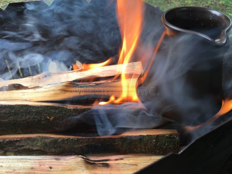 Café chez la dinde sur le bois de chauffage sur le bois du feu photographie stock libre de droits