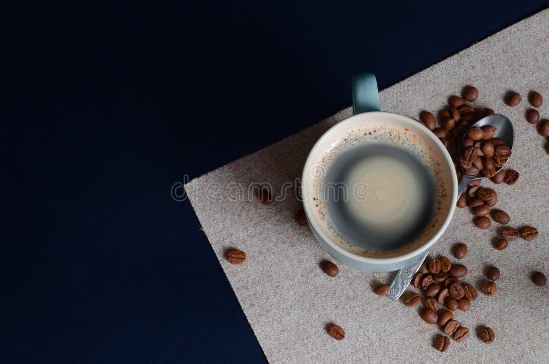Café colombien fort dans une tasse vert clair et un arabica entier de grains de café Vue supérieure photos libres de droits