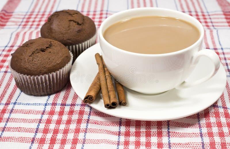 Café com leite, canela e queques foto de stock