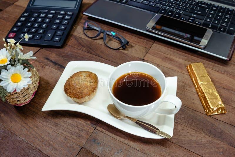 Café com o bolo do copo da banana e o equipamento de escritório no desktop imagem de stock