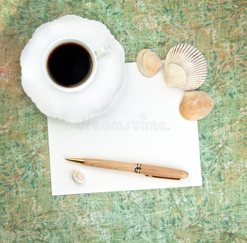 Café com papel, pena e escudos fotografia de stock