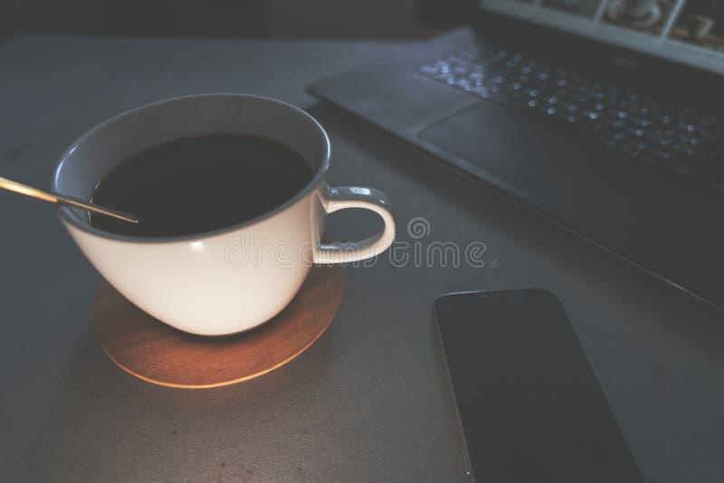 Café com portátil e o telefone esperto na tabela concreta fotos de stock