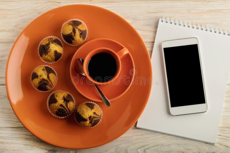 Café com queques, smartphone e um bloco de notas fotografia de stock