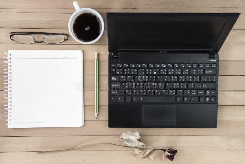 Café con el cuaderno, flor, lápiz, vidrios del ojo en el backgroun de madera imagen de archivo