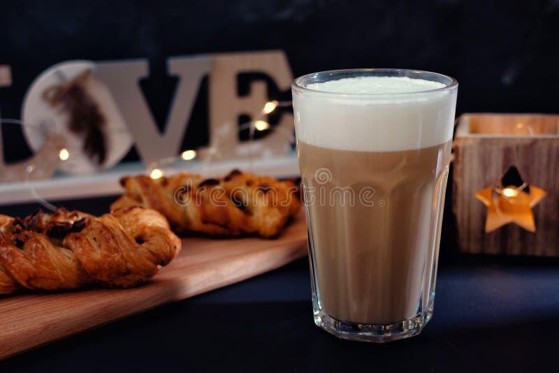 Café con espuma de la leche Al lado de un postre delicioso con el chocolate foto de archivo