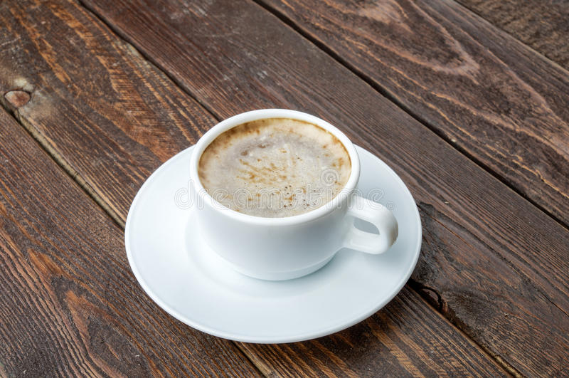 Café con espuma en la tabla de madera oscura fotos de archivo libres de regalías