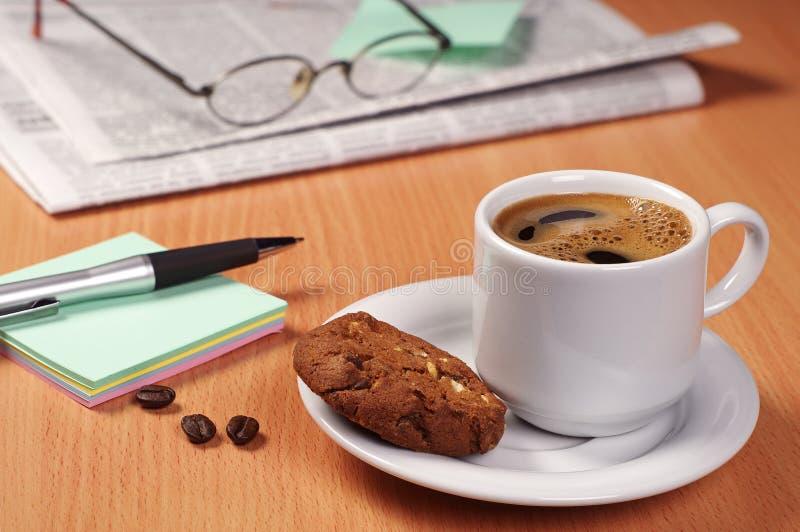 Café con la galleta, el periódico y la nota imagenes de archivo