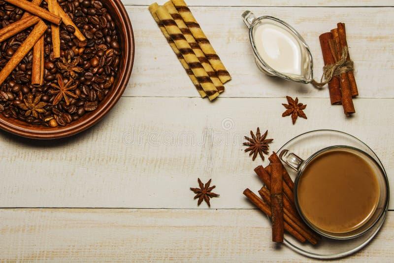 Café con las galletas de la leche, canela, anís en una tabla blanca de madera Visión desde arriba imagen de archivo