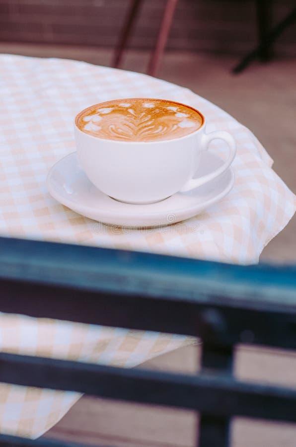 Café con los soportes de la espuma en una tabla con un mantel a cuadros fotografía de archivo libre de regalías