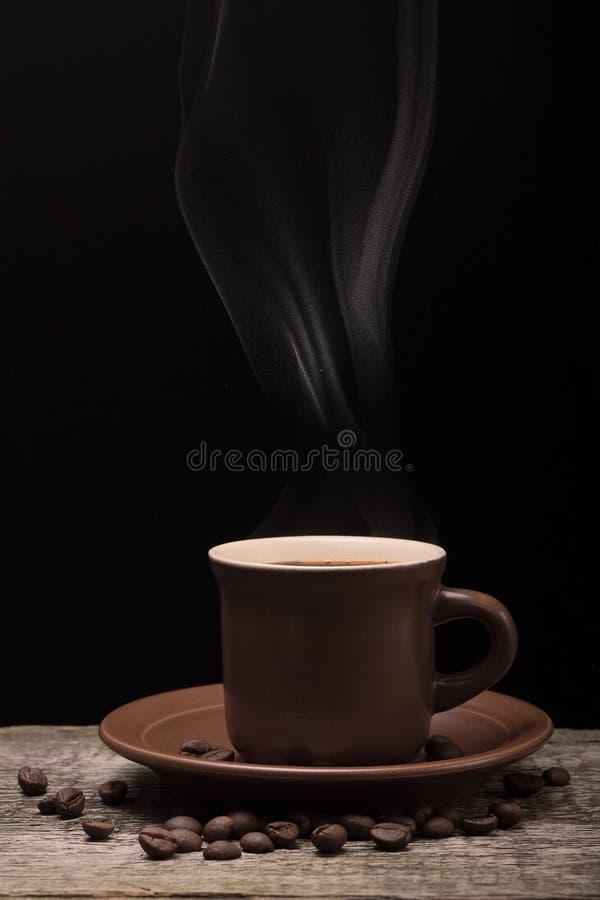 Café con vapor y habas en fondo negro imagen de archivo libre de regalías