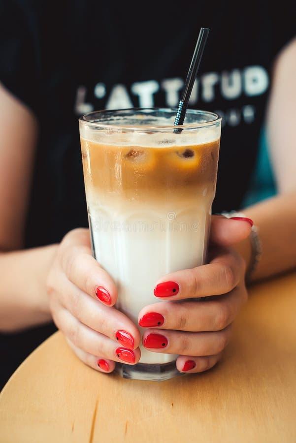 Café congelado com leite Latte congelado do café Mulher que guarda o copo de vidro do café congelado Estilo mínimo do tratamento  fotografia de stock royalty free